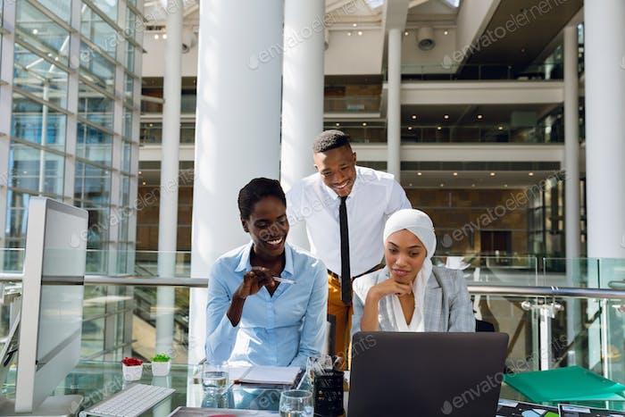 Männliche und weibliche Führungskräfte diskutieren über Laptop am Schreibtisch