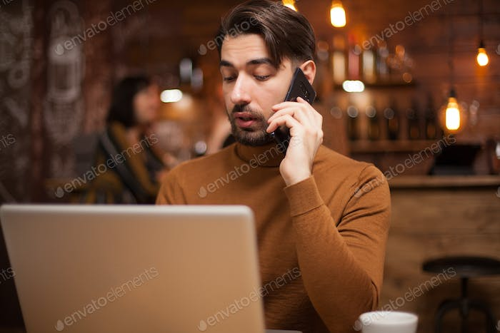 Smart businessman talking on the phone while browsing on his laptop