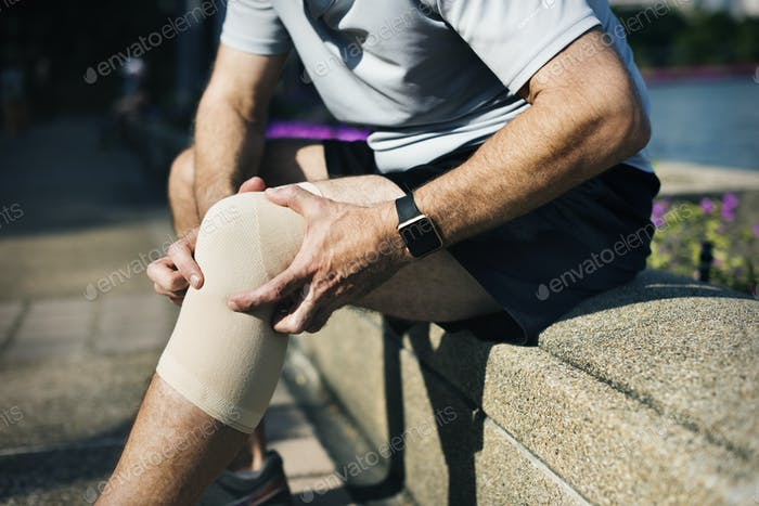 Elderly man having a knee injury