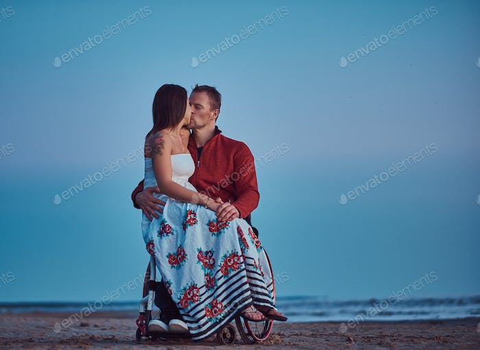 Woman sits on her husband's lap, resting on a beach against a background of a bright dawn.