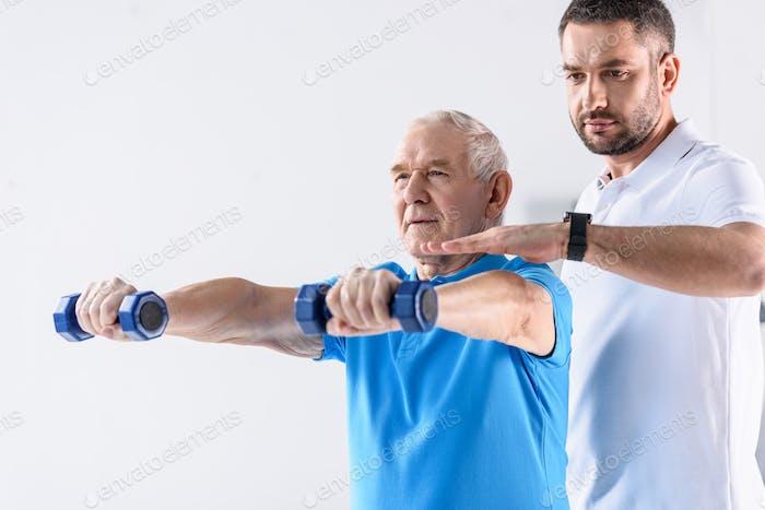 portrait of rehabilitation therapist assisting senior man exercising with dumbbells on grey backdrop
