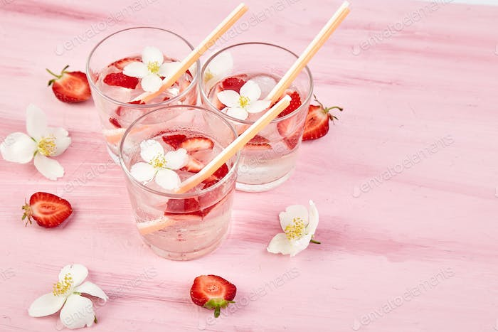 Strawberry detox water with jasmine flower. Summer iced drink or tea.