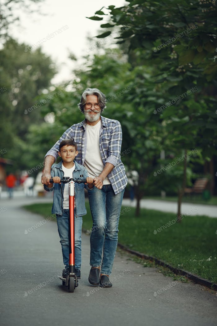 Grandfather with grandchild walking in a summer park