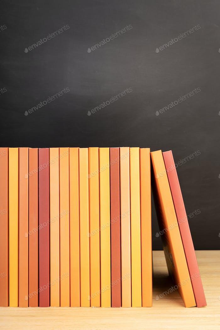 Group of orange books on wooden shelves