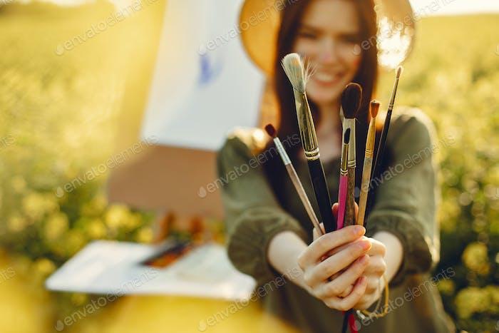 Elegante und schöne Mädchen Malerei in einem Feld