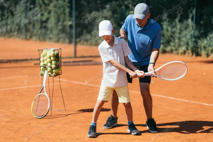Boy Learning to Play Tennis