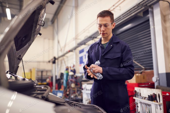 Male Motor Mechanic Wiping Hands After Working On Car Engine In Garage
