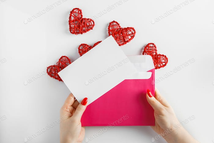 Envelope with a letter in hands on a white background