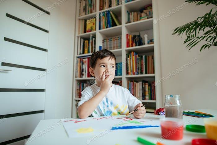 Vorschüler auf der Suche nach Inspiration beim Malen.