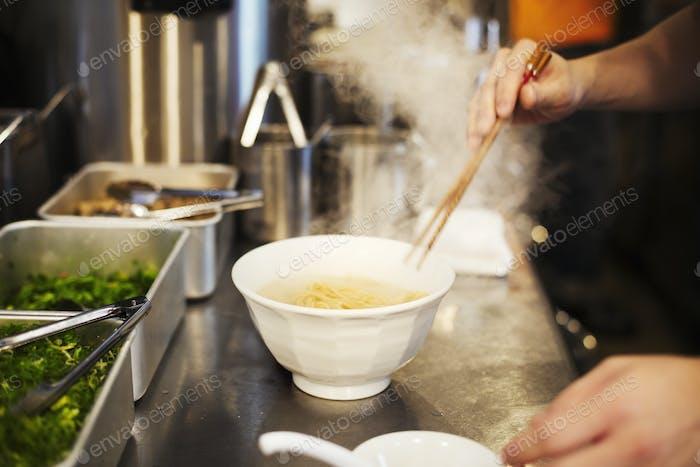 Eine Ramen-Nudel-Ladenküche. Ein Küchenchef bereitet Schalen mit Ramen-Nudeln in Brühe, eine Spezialität und schnell