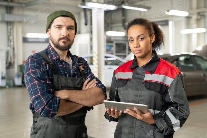 Two young serious workers of car maintenance center in uniform working in hangar