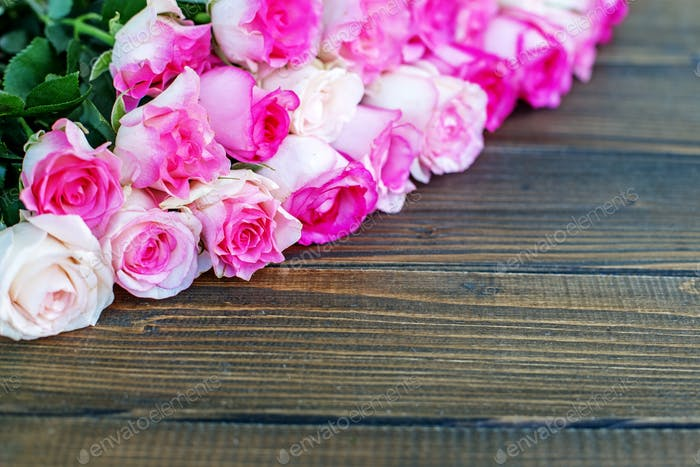 Wooden background with pink roses. A place for congratulations