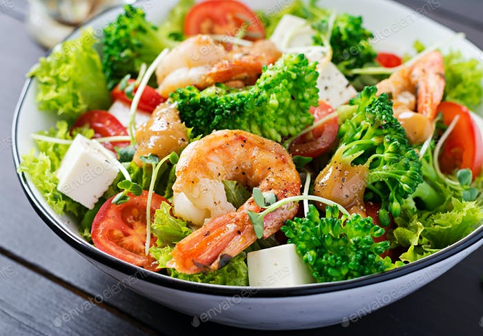 Salat mit gegrilltem Lachs, Salat, Avocado, Tomaten und Mais auf einer weißen Schüssel.