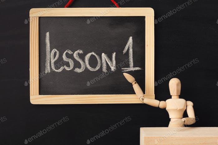 Lesson 1 written with chalk on blackboard.
