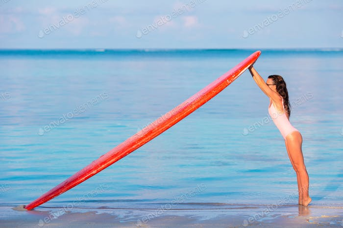 Happy beautiful surfer girl at the beach with her surfboard