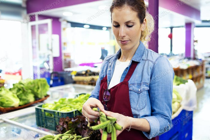 Saleswoman selecting green beans and preparing for working day i
