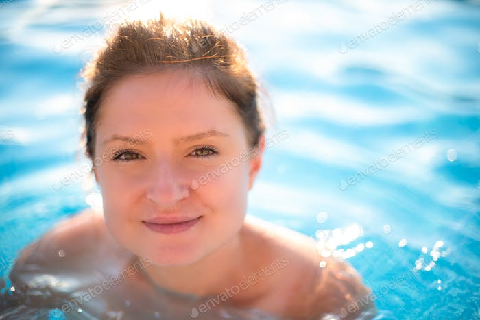 Young woman portrait in swimming pool.