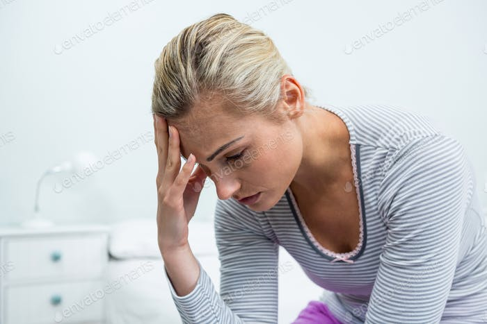 Upset woman with headache at home