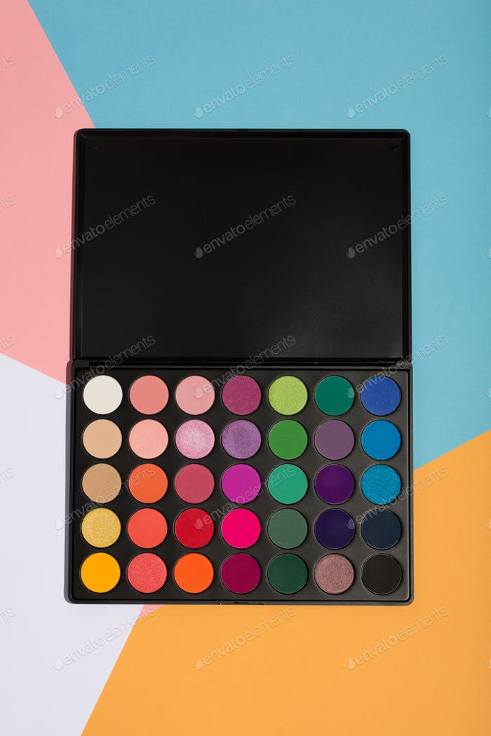 Makeup palette on a colorful geometrical background.