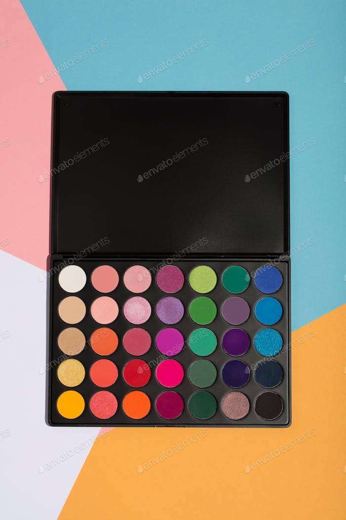 Make-up-Palette auf einem bunten geometrischen Hintergrund.
