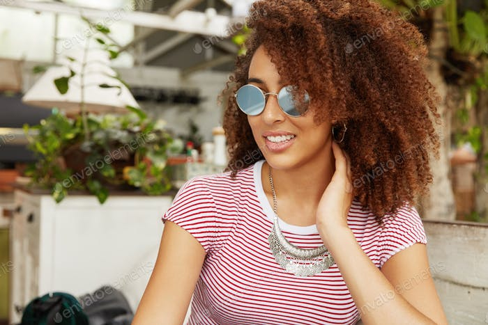 Sideways portrait of cheerful African American female in shades, looks thoughtfully and pleased away