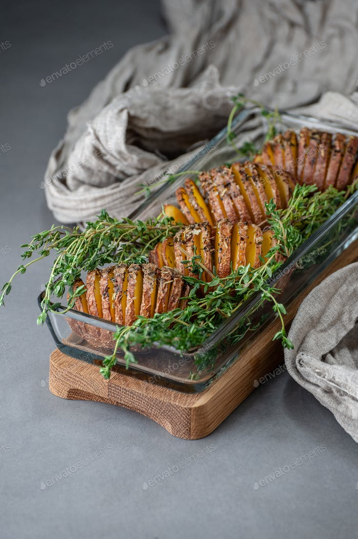 Baked potatoes with thyme in a glass container on a gray stone t