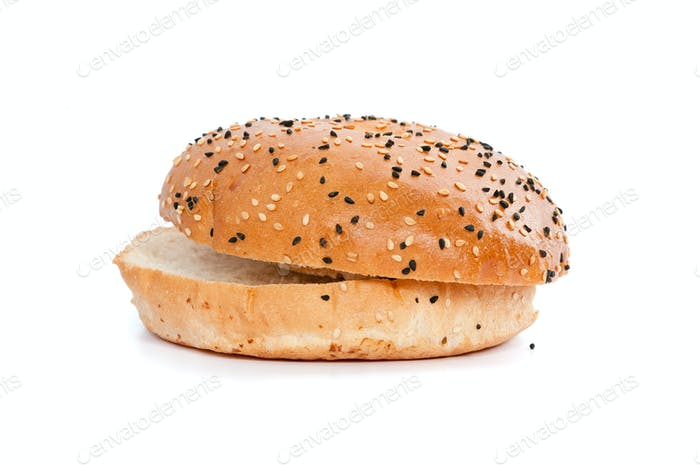 Burger bun with sesame seeds on white background