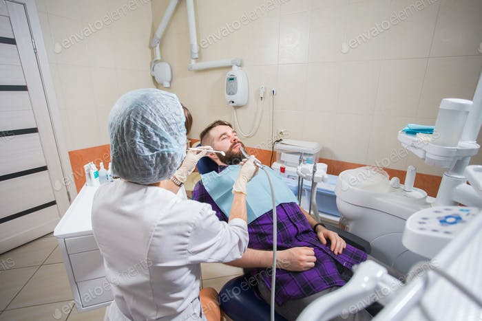 Female dentist with male patient at clinic. Dentistry, stomatology and dental health concept