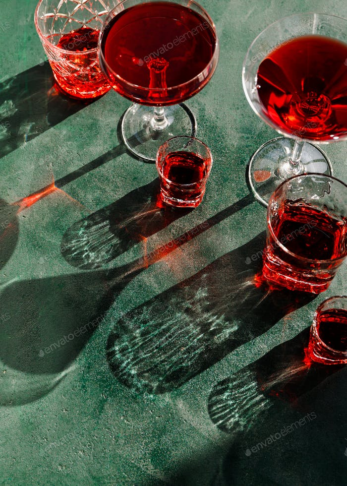Creative beverage photography of red cocktail in different glasses under hard light