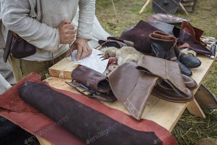 Craft shoemaker demonstrates shoes, tools and leather at cobbler workplace on festival workshop