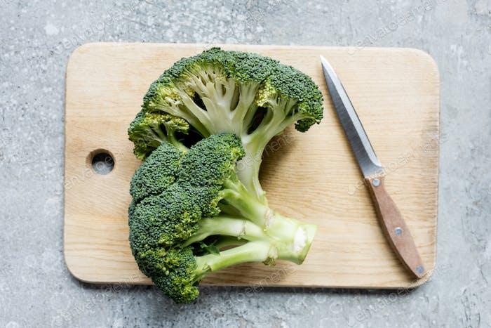 Draufsicht von frischem grün geschnittenem Brokkoli auf hölzernem Schneidebrett mit Messer auf grauer Oberfläche