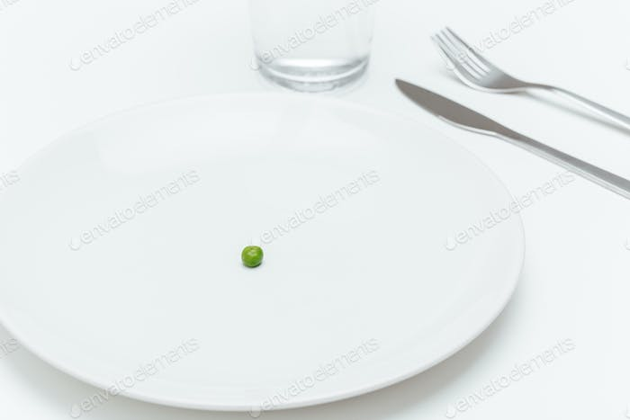 Plate with one small green pea on served table