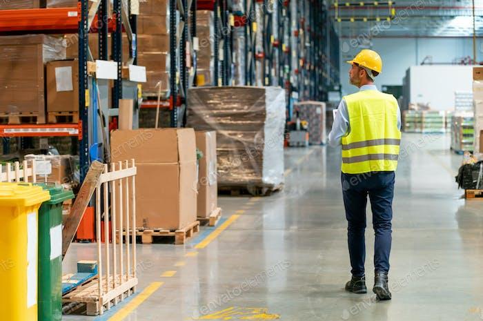 Trabajador de almacén con portátil e introducción de datos en la base de datos