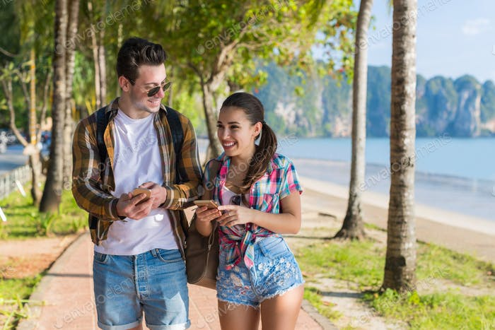 Casual Couple Use Cell Smart Phones In Tropical Palm Trees Park, Happy Smiling Beautiful Young