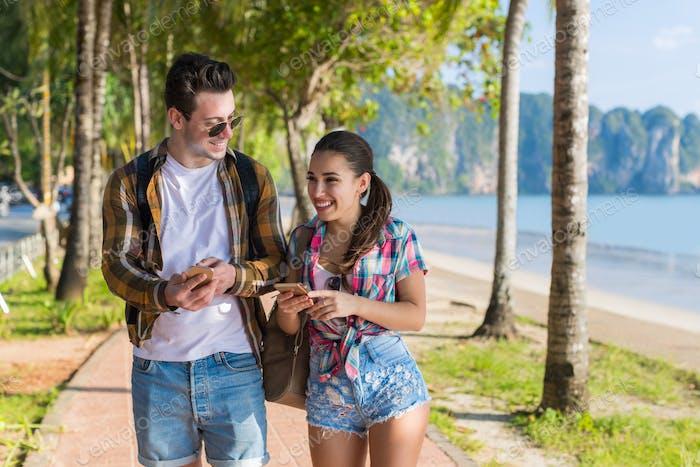 Casual Paar Verwenden Handys In Tropischen Palmen Park, Glücklich Lächeln Schön Jung