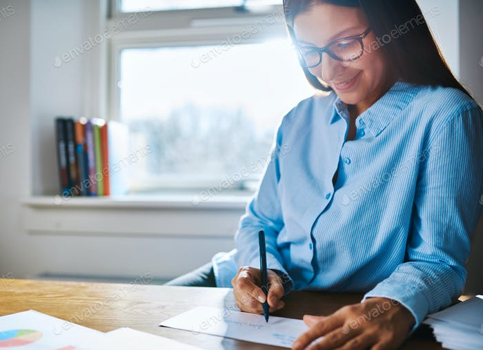 Happy entrepreneur writing at desk