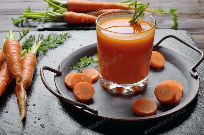 Vegetarian background of old tray with carrots and juice on slat