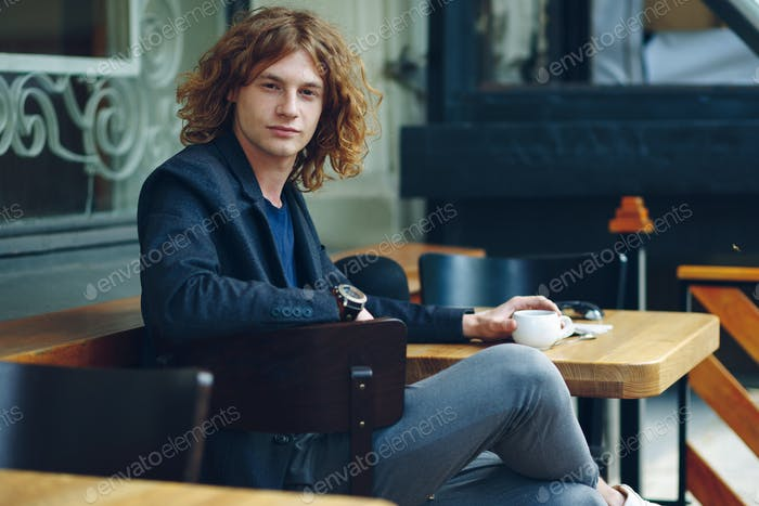 Portrait interesting reddish man posing with coffee