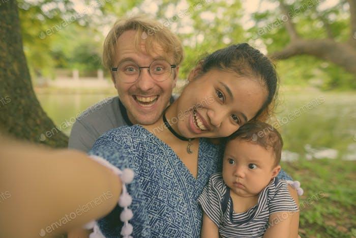 Multiethnische junge Familie verbindet sich im Park