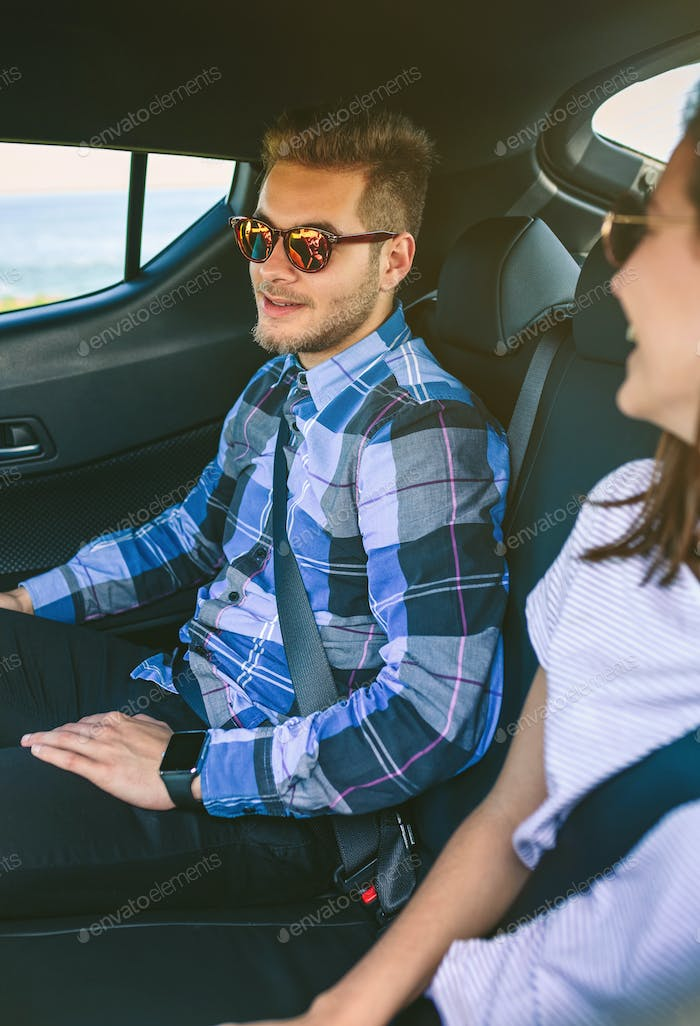 Young couple traveling by car with seat belts on