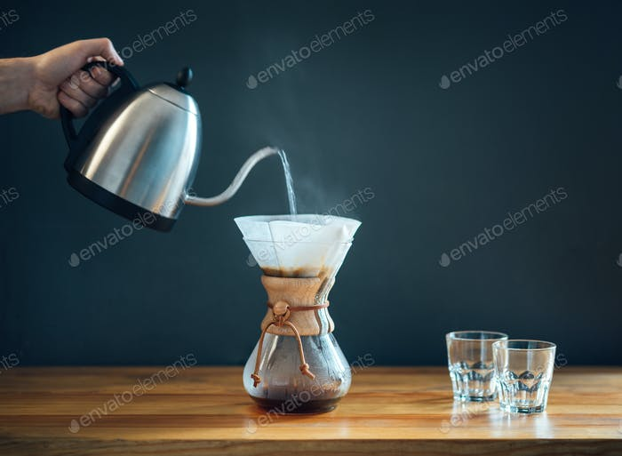 making coffee by an alternative method, pouring hot water from kettle into a glass decanter