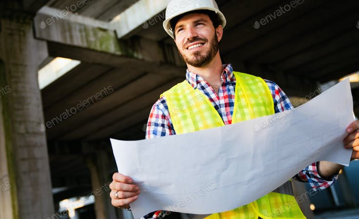 Picture of construction site engineer looking at blueprint