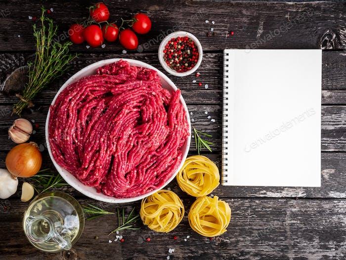 Hackfleisch, Hackfleisch mit Zutaten zum Kochen auf dunkelblau