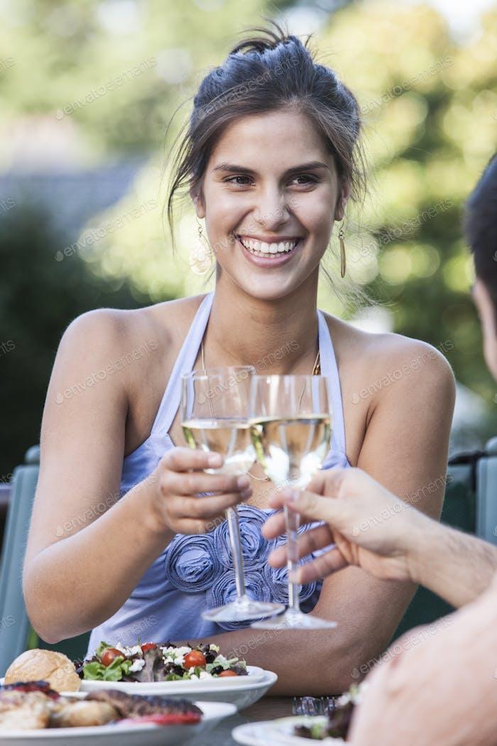 Hispanic Paar mit einer gesunden Mahlzeit und ein Glas Weißwein.