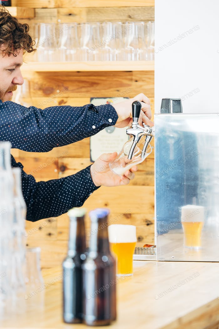 Bearded man filling up the glass