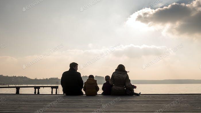 Junge Familie sitzt auf einem Holzdeck bei Sonnenuntergang