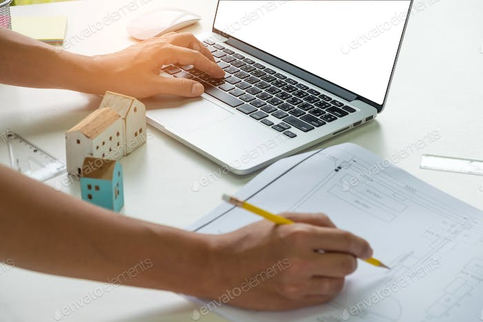 Architects are writing on the desk other hand uses a laptop.