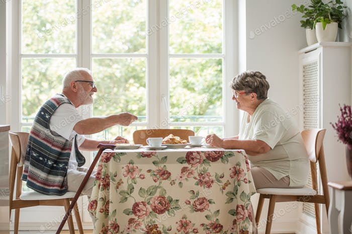 Senior couple sitting together at table drinking tea and eating cake