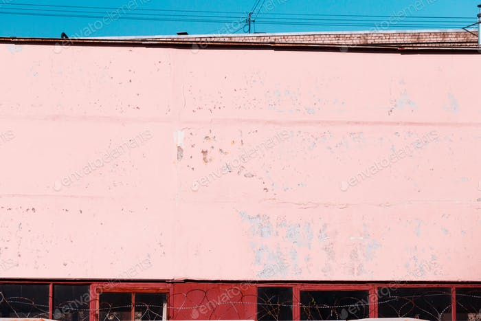Pink textured concrete wall of an old building.