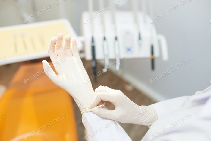 Crop dentist putting on white gloves